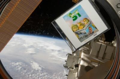 """עותק הסרט """"פלנט 51"""" בתחנת החלל. הצילום מעתיק שוט מתוך הסרט בו רואים את לם, חייזר מפלאנט 51, מתבונן בפעם הראשונה על הכוכב שלו מחלונה של חללית."""